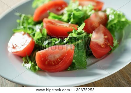 fresh summer salad with tomatoes, rucola and frillis leaves in plate on wood table, shallow focus