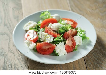 fresh summer salad with tomatoes, rucola, frillis and mozzarella in plate on wood table, shallow focus