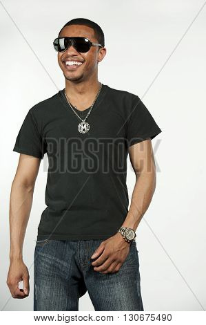 A happy young hip African American male wearing a black t-shirt with sunglasses in a studio setting on a white background.