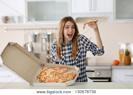 Happy young woman holding hot pizza in box at home