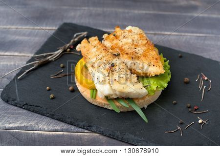 Fishburger with pepper and salat lettuce on the stone plate