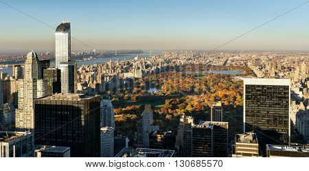 Panoramic aerial view on Central Park in fall colors with Midtown skyscrapers, Upper West Side buildings and the George Washington Bridge in the distance. Manhattan, New York City