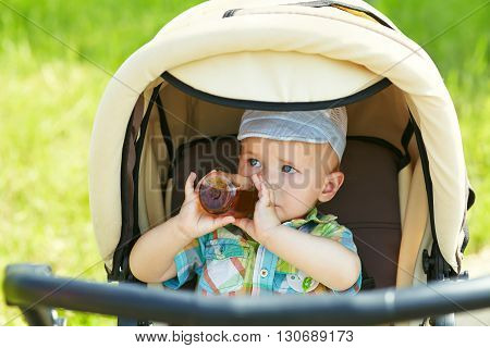 little boy sitting in a stroller and drinks from a bottle. baby for a walk in a pram. summer outdoors