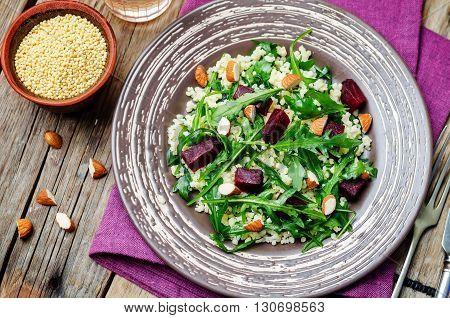 beet millet almonds arugula salad on wooden background