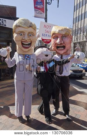 Asheville, North Carolina, USA - February 28, 2016: Parody of Donald Trump and Hillary Clinton characters happily taking bags of money from Mr. Monopoly in front of a Bernie Sanders sign saying Bernie is not for sale on February 28 2016 in Asheville