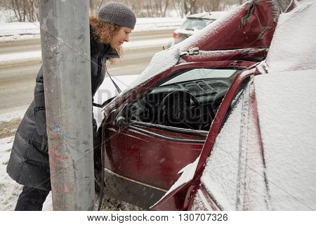 Young woman dressed in winter coat looks into driver cabin of damaged car.