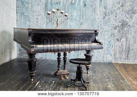 Old black grand piano stands in room with ragged walls and floor.