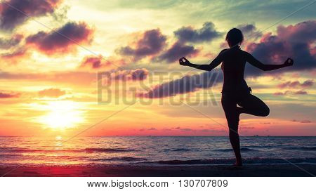 Yoga silhouette at surreal bloody sunset on the sea shore. Calm and self-control.