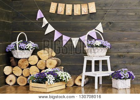Pile of firewoods, wooden box and wicker baskets with flowers inside shed.