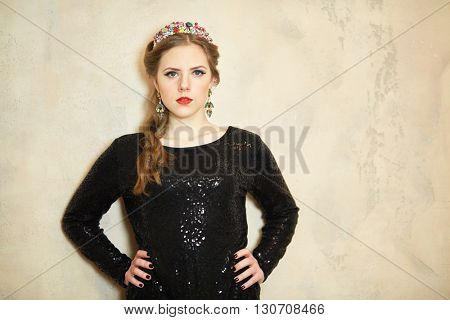 Young woman in dark knitted dress stands with her arms akimbo at wall in studio.