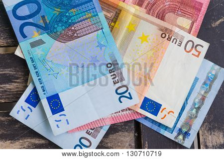Pile of euro bank notes detail photo. Detail of ten twenty and fifty euro bank notes on wooden background. Paper money on wooden background.