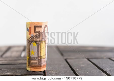 Standing roll of 50 euro bank notes. Detail roll of fifty euro bank notes (or bills) on wooden background. Paper money on wooden table.