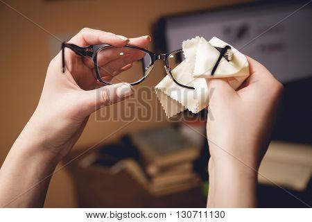 Female hands rubs black-rimmed spectacles special sponge