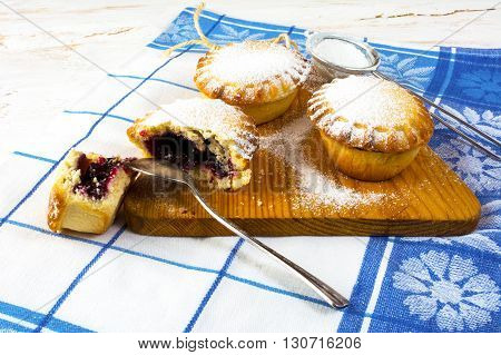 Confiture pie on the cutting board. Sweet dessert. Sweet pastry. Small pie. Pie. Jam pie