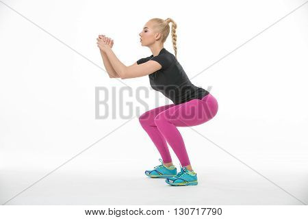 Sportive blonde gymnast in the sportswear squats on the white background in the studio. Shoot from the side. She wears cyan-yellow sneakers, pink pants and black t-shirt. She holds her hands raised in the lock. She looks on her hands. She has a plait on h