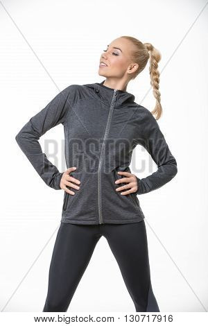 Sportive blonde girl in the sportswear stands on the white background in the studio. She wears black-gray pants and gray hoody. She holds her hands on her waist. She looks to the right with a smile. She has a plait on her head. Vertical.