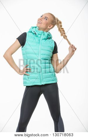 Pretty blonde girl in the sportswear stands on the white background in the studio. She wears black-gray pants, black t-shirt and mint vest. She holds her right hand on her waist. She holds her plait with left hand. She looks to the right and up with a smi