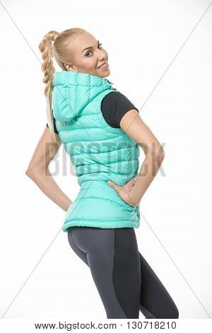 Sexy blonde girl in the sportswear stands with her back to the camera on the white background in the studio. She wears black-gray pants, black t-shirt and mint vest. She holds her hands on her waist. She has a plait on her head. She looks into the camera