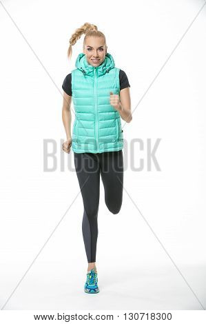 Smiling blonde girl in the sportswear runs on the white background in the studio. She wears cyan-yellow sneakers, black-gray pants, black t-shirt and mint vest. Left leg is in the air. She has a plait on her head. She looks into the camera. Vertical.