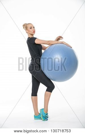 Blonde girl in the sportswear stands sideways with a blue fitball on the white background in the studio. She wears cyan-yellow sneakers, black pants and black t-shirt. She holds the fitball while it is on her right thigh. Her right leg is on the toe. She
