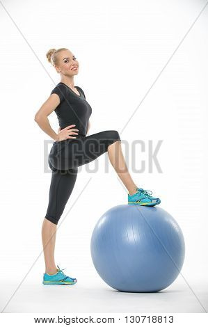 Sportive blonde girl in the sportswear stands sideways with a blue fitball on the white background in the studio. She wears cyan-yellow sneakers, black pants and black t-shirt. She holds hands on her waist. Her right leg is on the fitball. She looks into