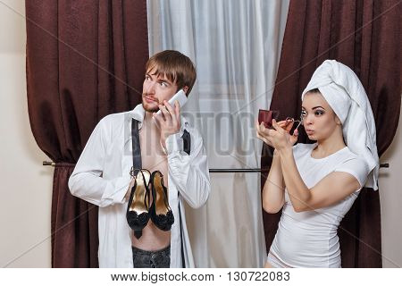 Morning couples. Husband and wife are going to party. Man talking on the phone and holding her shoes. Girl doing make-up with a towel on her head.