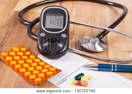 Medical pills tablets or supplements for therapy prescription glucose meter and stethoscope on desk in doctor office concept of diabetes treatment and health care