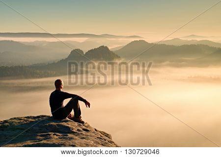 Hiker in black on the rocky peak. Wonderful daybreak in mountains heavy mist in deep valley. Man sit on the rock. poster