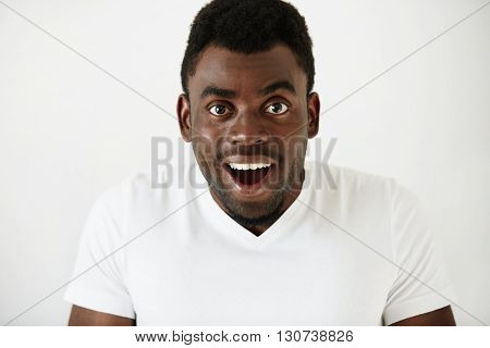 Close Up Of Amazed Young African American Man In White Blank T-shirt, Having Fun Indoor, Looking At