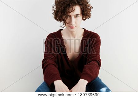 Portrait Of Sensual Young Brunette Woman Wearing Cleavage-baring Casual Cardigan And Blue Jeans Sitt