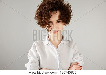 Close Up Portrait Of Outraged Young Brunette Woman With Short Curly Hair Cut Standing With Arms Cros