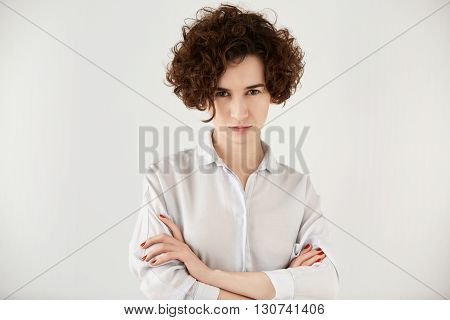 Portrait Of Young Vexed Brunette Woman Standing With Arms Folded Against White Concrete Wall Backgro