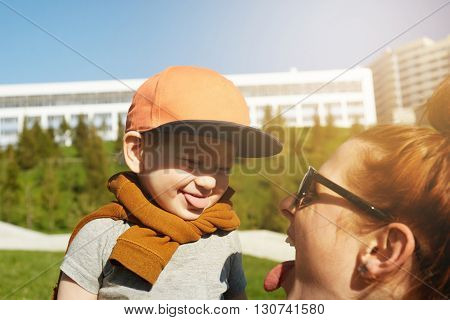 Portrait of adorable two-year old toddler wearing stylish clothes and cap showing tongue to her young mother. Redhead woman holding her son against green park background. Film effect flare sun