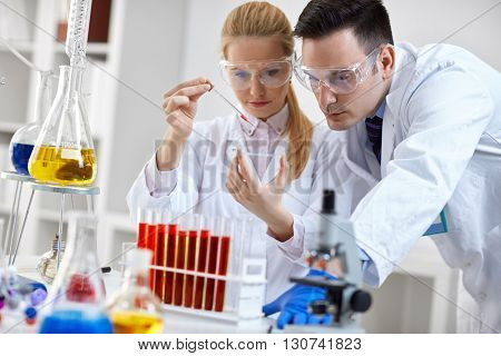 two student looking at a microscope slide in a laboratory