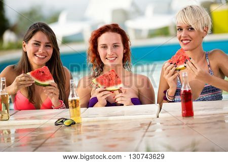 Cute redhead, brunette and blond famine posing with pieces of watermelon and drinks near edge of swimming pool