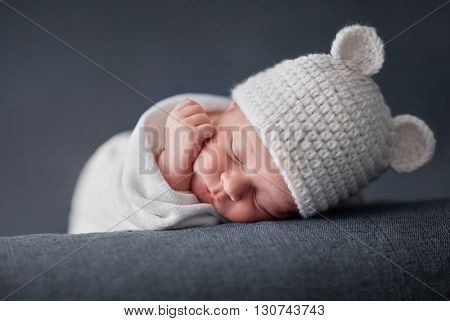 Newborn baby 2 weeks old sleeping on soft blue  fluffy blanket with funky woolen hat