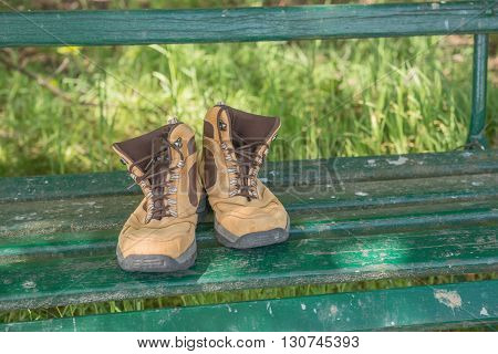 Hiking shoes on green bench in the forest