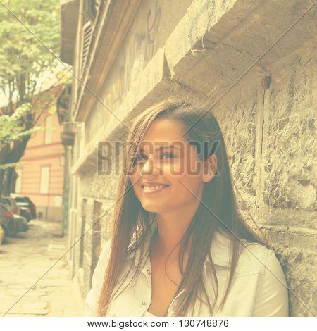 Cute girl posing on a classic European street.