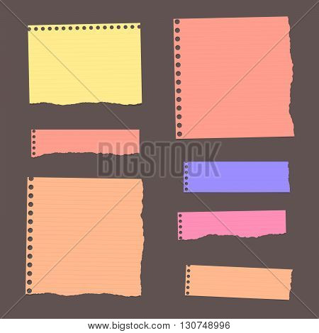 Colorful ripped lined blank note paper are stuck on dark wall.