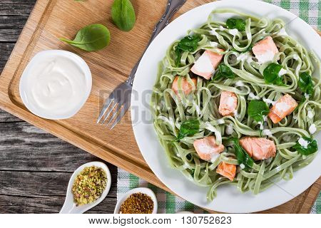 Salmon and Spinach Fettuccine pasta on white dish and table napkin cream sauce in gravy boat spices and pistachios in porcelain Chinese style sauce spoon on a wooden table studio lights top view