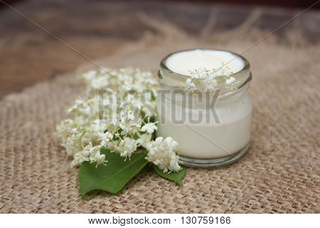 Face cream in a glass jar with chestnut flowers on a background of burlap.Cosmetics.
