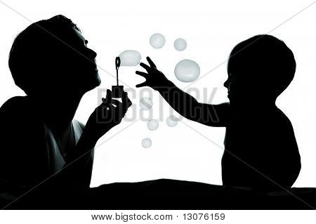 1 year old baby and his mother are playing together with bubbles. They are silhouetted.