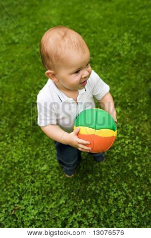 One year old baby is playing with a ball on the green.