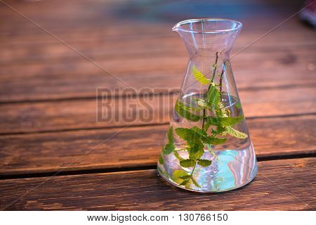 Water With Peppermint Leaves In Carafe On Wooden Ground