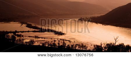 This is a sunset landscape with river in the valley. The IRL location is the bend of Danube in Hungary during a the most higher flood in the past 100 years.