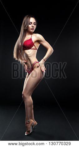 Beautiful curvaceous brunette woman posing in a red bikini on an gray studio background.