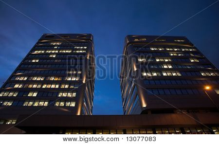 A night-time officebuilding with lights in the windows.