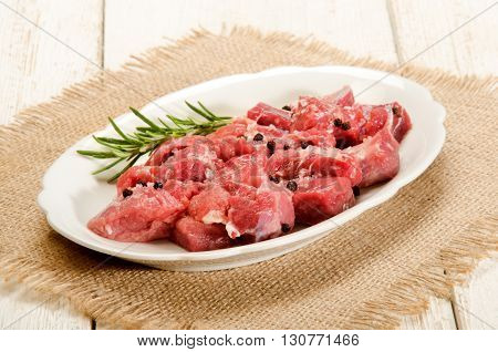 preparation of raw deer goulash with rosemary peppercorn on an oval kitchen plate