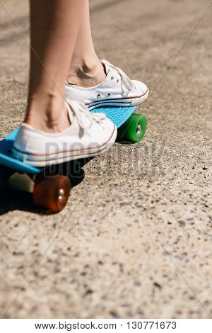 Young Girl In Sneakers On Skateboard.