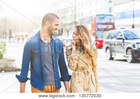 Multiracial couple walking in London. He is middle eastern she is caucasian both are smiling and looking each other. They could be friends or in a relationship. Lifestyle and love concepts.
